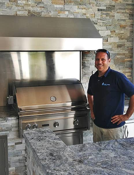 OWNER OF GRILL TANKS PLUS IN FRONT OF OUTDOOR KITCHEN